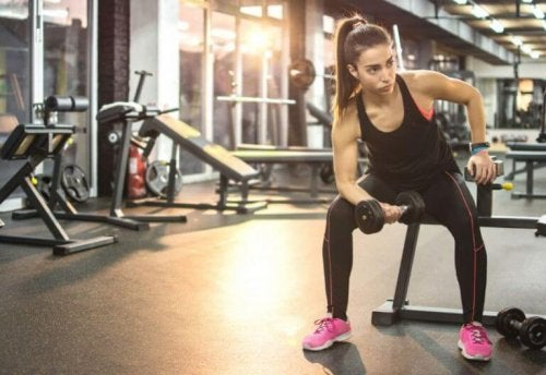 Sports motivation woman on bench with dumbbell