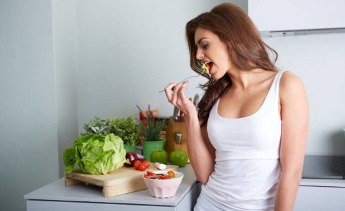 Woman eating salad with ingredients