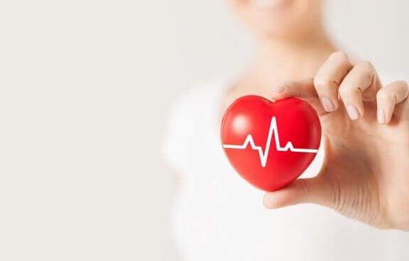 kvinde der holder en hjertefigur med hjertefrekvens