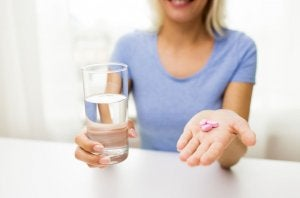 Woman holding water and diet pills