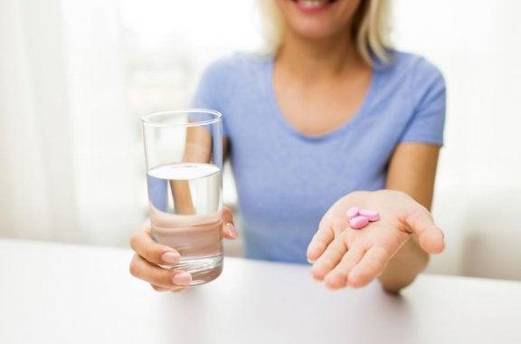 kvinde med et glas vand i den ene hånd og piller i den anden