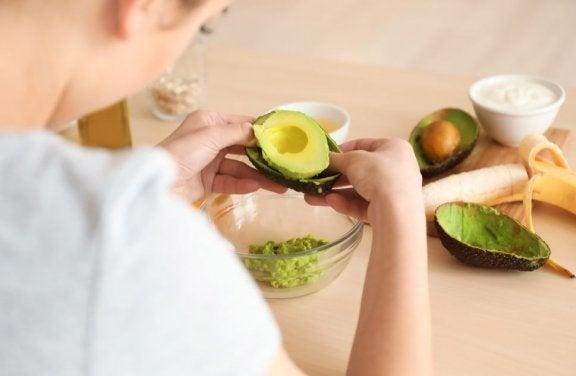 en kvinde der piller indmad ud af en avocado