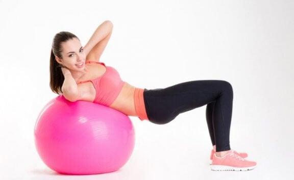 kvinde der laver maveøvelse på pink bold