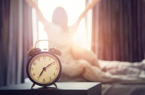 gammeldags vækkeur og en kvinde der strækker sig