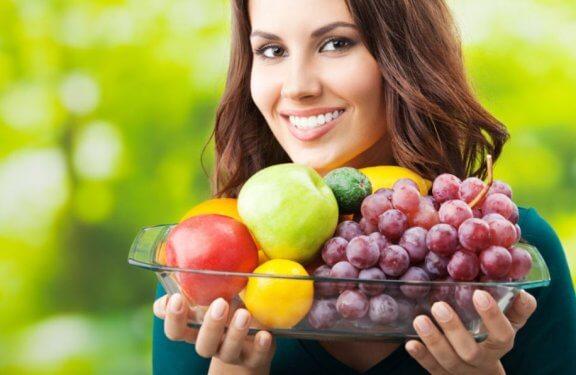 kvinde der holder et glasfad med lækker, frisk frugt