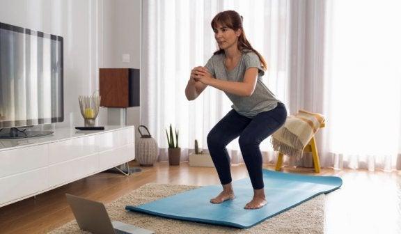 kvinde der laver squats på en måtte derhjemme