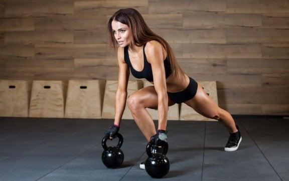 kvinde der træner med kettlebells