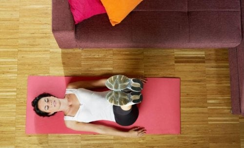Work out at home woman doing yoga on floor with legs extended