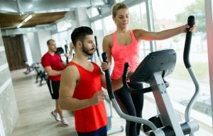Personal trainer showing how to exercise with elliptical.