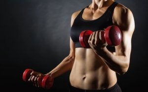 Woman increasing training frequency with dumbbells.