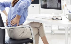 Woman with back pain for not doing exercise.