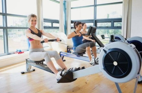 Three women in a gym using rowing machines with good technique