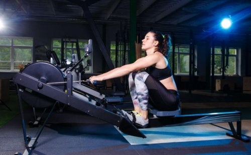 Woman using a rowing machine in a dark gym showing the rowing mistakes to avoid