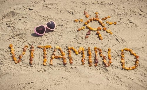 Vitamin D spelled out in sand on beach