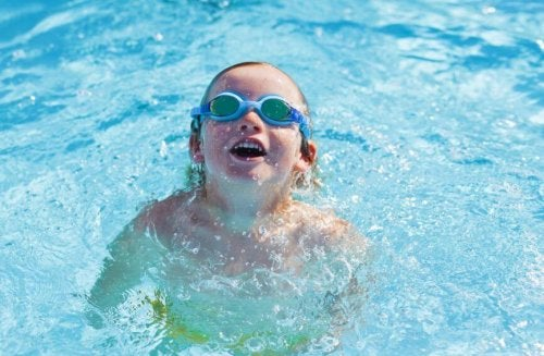 Child with goggles swimming in pool smiling