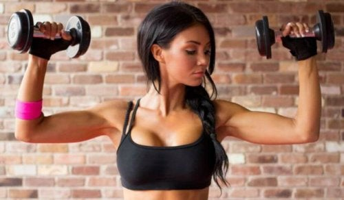 Woman using handweights to train arms in gym female bodybuilding