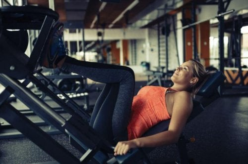 A woman performing a leg press in the gym.