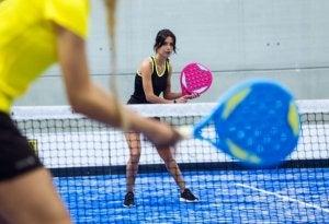 Two women playing padel racket.