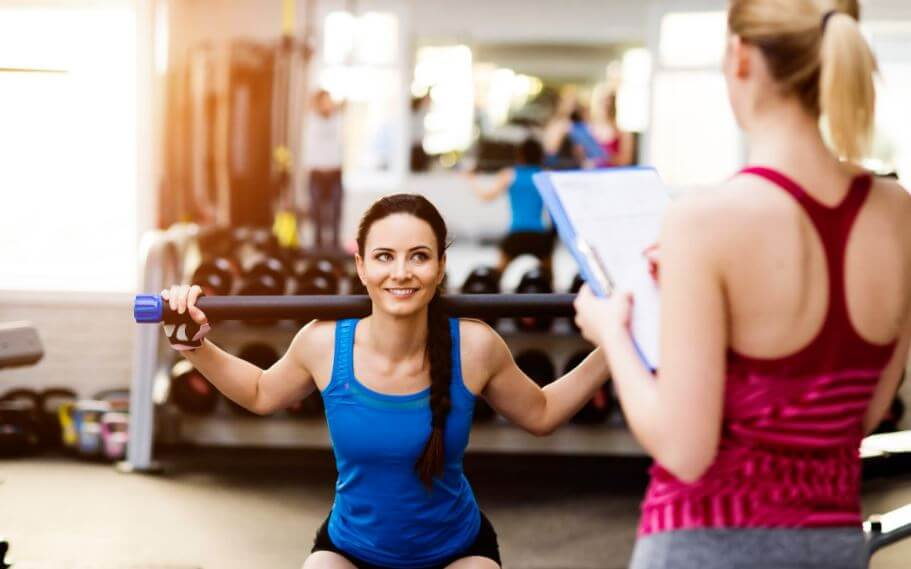 woman in gym with trainer