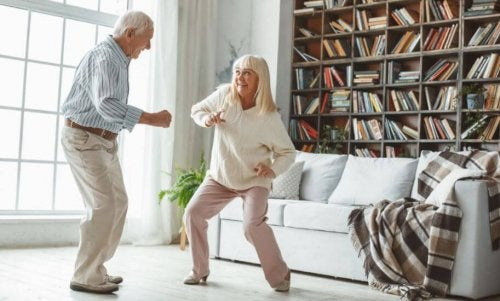 Elderly couple dancing together at home using app bailonga