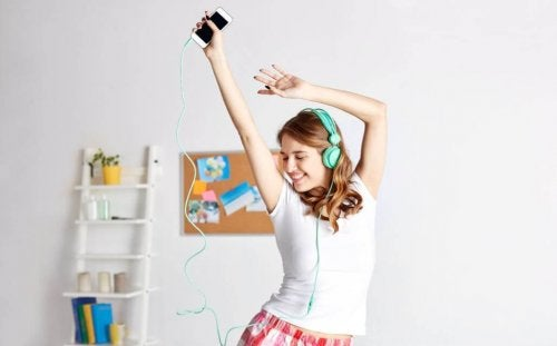 Young woman dancing at home with phone and headphones bailonga application