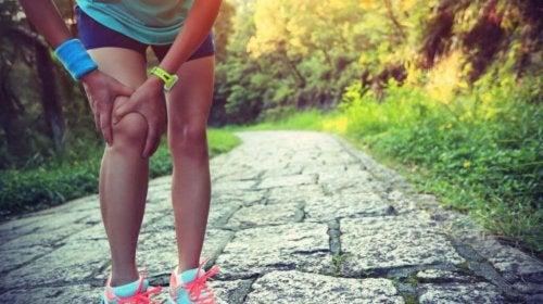 Woman grabbing injured leg kinesiology tape prevent injury