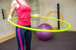 Woman trying to burn fat with hoop.