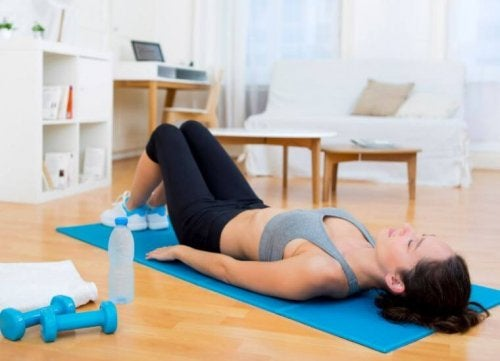 Woman doing yoga back on floor knees bent postpartum exercises