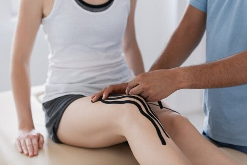 Kinesiology tape for taping the knee of a woman