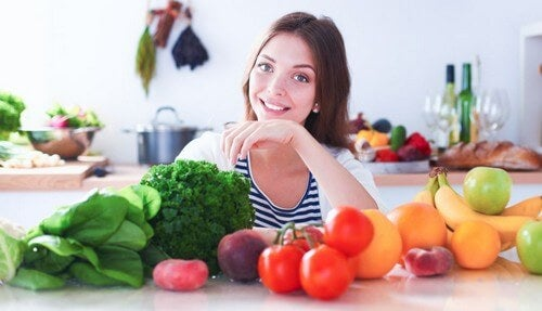 Woman smiling with fruits and vegetables