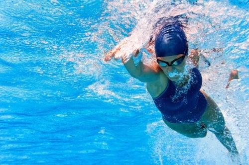 Woman swimming front crawl in pool