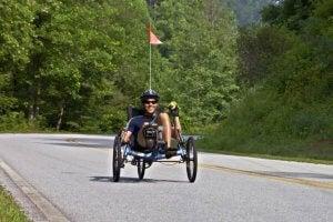 Man riding a recumbent bike on a road