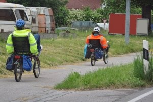 Two people riding recumbent bikes in the countryside