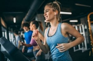 Woman using a heart rate monitor as she runs on the treadmill