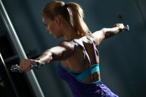 Woman doing lateral raises with dumbbells to strengthen her back