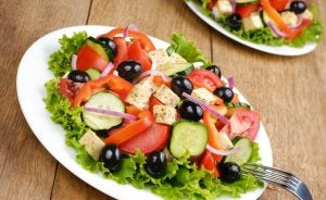 A greek salad with a lot of olives