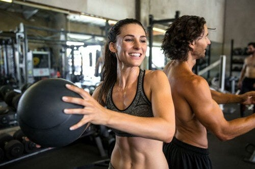 Man and woman training medicine balls