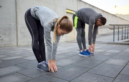 Man and woman stretching outside stretches for tight hamstrings
