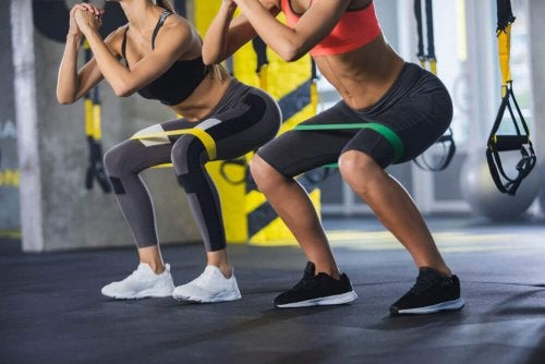 woman doing squats with elastic bands