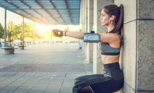 Woman listening to music doing squats against the wall during sunset