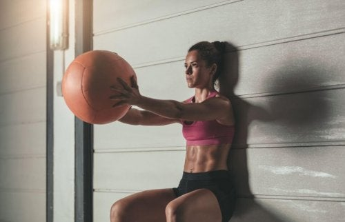 Woman using a weighted ball to do squats against the wall