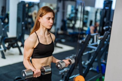 Woman doing bicep curls with dumbbells at gym