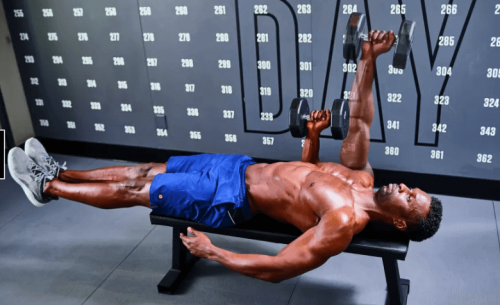Man laying on bench in gym doing a single-arm larsen press with dumbbells