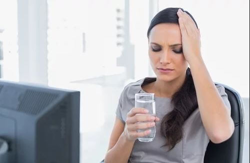 Woman sitting at desk drinking water headache dehydrated due to too much cardio