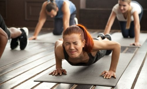 Woman doing planks forcing straining herself in a gym class