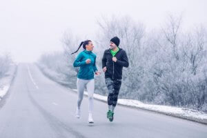 Couple running outside in winter.