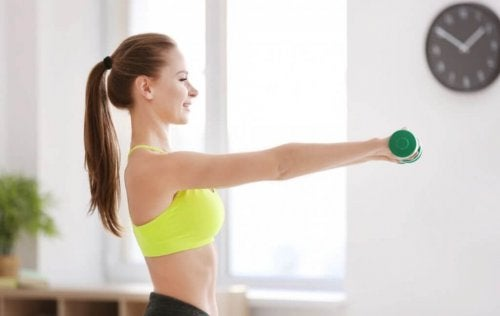 Woman lifting weights strengthening arms bodybuilding at home