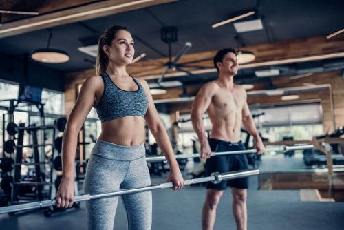 Woman and man in gym lifting bar for exercise strength training