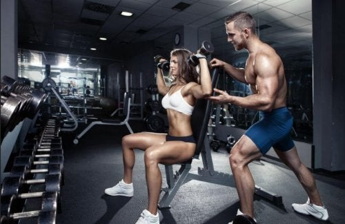 Couple in an empty gym doing military press with dumbbells