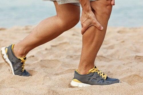 Man grabbing leg cramp